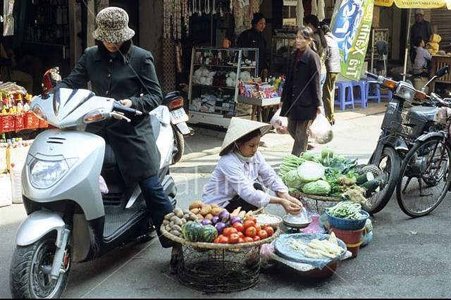 A9BHTB Young woman on motor scooter buying vegetables from street vendor at Ngo Sy Lien St market, Dong Da, Hanoi, Viet Nam. Image shot 2004. Exact date unknown.